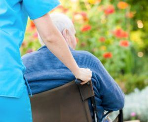 Nurse helping elderly man at nursing home in Long Island.
